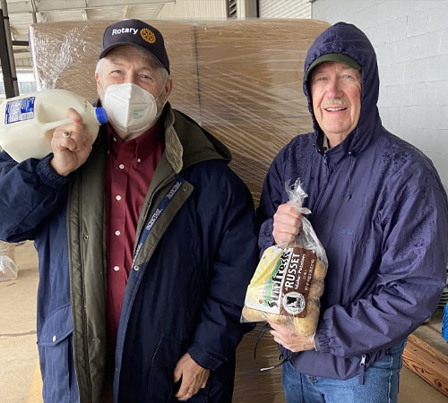 Rotary President Max Caylor slings a milk jug while Club Secretary John Sneve holds a bag of potatoes.