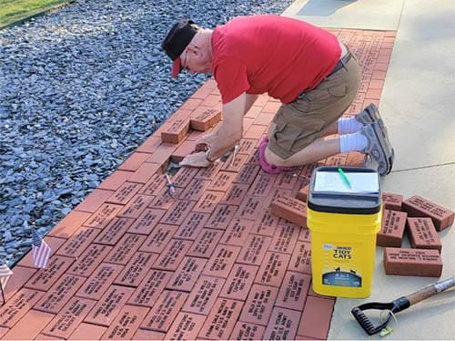 Gary Bledsoe Chairman of Bricks of Honor placing new Bricks of Honor at the Veterans Memorial.
